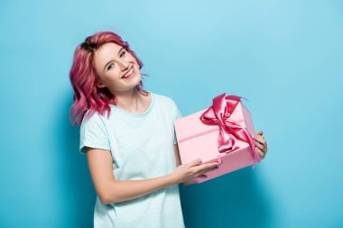 Young woman with pink hair holding gift box with bow and smiling on blue background stock vector