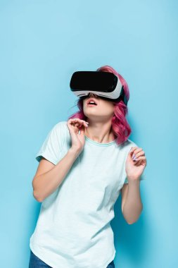 Scared young woman with pink hair in vr headset on blue background stock vector