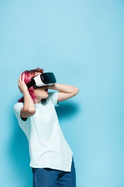 Shocked young woman with pink hair in vr headset holding head on blue background stock vector