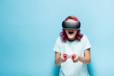 KYIV, UKRAINE - JULY 29, 2020: excited young woman with pink hair in vr headset holding joystick on blue background stock vector