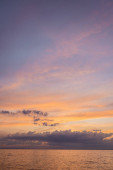Krajina moře a zatažená obloha při západu slunce