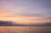Krajina oblačné oblohy a moře při západu slunce