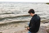 Muž v kožené bundě sedí na kameni na mořském pobřeží