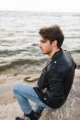 Muž v kožené bundě a džínách sedí na kameni na pláži