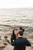 Vysoký úhel pohledu na mladého muže líbání přítelkyně v kůži jacker na pláži v blízkosti moře