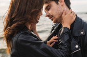 Young woman touching neck of boyfriend in leather jacket near sea