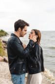 Boční pohled na mladého muže dotýkat brunetky přítelkyně v kožené bundě na pobřeží