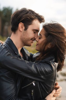Young man kissing brunette girlfriend in leather jacket outdoor stock vector