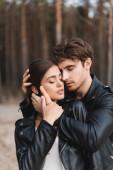 Mladý muž se zavřenýma očima objímající brunetku přítelkyně v kožené bundě v blízkosti lesa