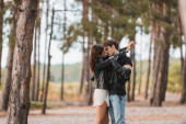 Selektivní zaměření mladých párů v kožených bundách líbání v lese