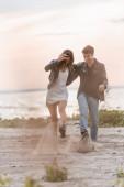 Selektiver Fokus eines jungen Paares, das bei Sonnenuntergang Sand auf den Meeresgrund wirft