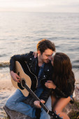 Young couple in leather jackets with acoustic guitar sitting on beach during sunset