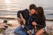 Bruneta žena objímání přítel v kožené bundě s akustickou kytaru na pobřeží večer