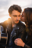 Brunette woman kissing man in leather jacket with acoustic guitar at sunset