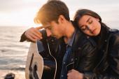 Mladý muž drží akustickou kytaru v blízkosti ženy na pláži při západu slunce