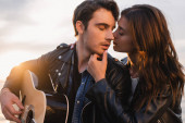 Brunette woman kissing boyfriend in leather jacket with acoustic guitar during sunset