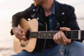 Oříznutý pohled na mladého muže hrající na akustickou kytaru venku