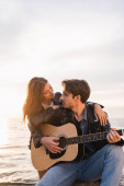 Mladá žena v kožené bundě objímající přítel hraje akustickou kytaru v blízkosti moře při západu slunce