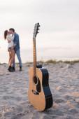 Selektivní zaměření akustické kytary na písek a mladé páry líbání na pláži při západu slunce