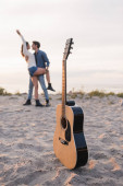 Selective focus of acoustic guitar on sand near young couple embracing on beach at sunset