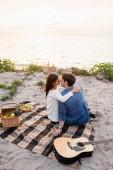 Selektivní zaměření páru líbání v blízkosti akustické kytary při pikniku na mořském břehu při západu slunce