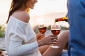 Ausgeschnittene Ansicht einer Frau mit Gläsern, während ihr Freund am Abend Wein am Strand einschenkt