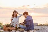Pár hraje na akustickou kytaru během pikniku s vínem na pláži při západu slunce