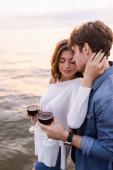 Bruneta žena drží sklenici červeného vína a dotýká krk přítele u moře