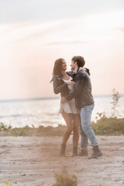 Selective focus of young couple in leather jackets hugging on beach at dawn stock vector