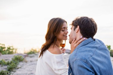 Selective focus of woman with glass of wine kissing boyfriend on beach stock vector