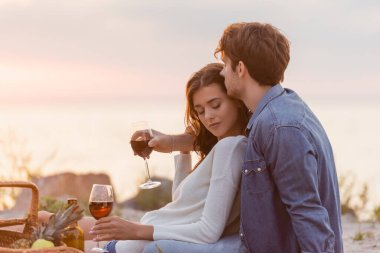 Selective focus of man hugging girlfriend with glass of wine during picnic on beach stock vector