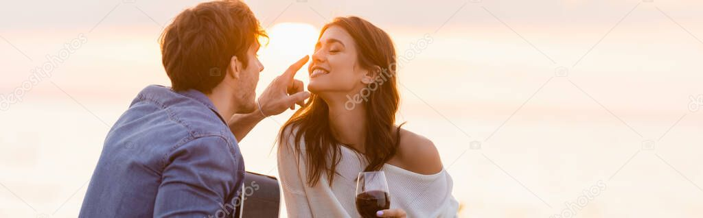 Panoramic shot of man with acoustic guitar touching nose of girlfriend with glass of wine near sea stock vector