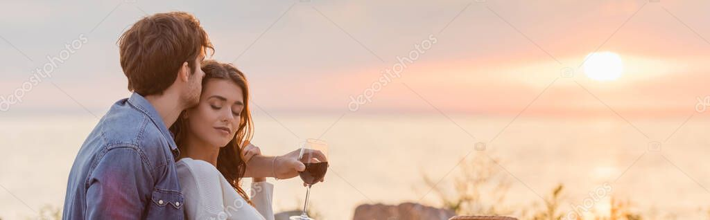 Panoramic shot of woman with glass of wine embracing girlfriend on beach at sunset stock vector