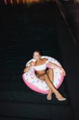 Junge Frau hält Einwegbecher in der Hand, während sie nachts auf Schwimmring im Schwimmbad sitzt