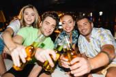 Selektivní zaměření mladých přátel cinkání s pivem venku v noci