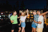 Young people dancing during party outdoors at night