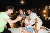Selektivní zaměření vzrušených mladých lidí cinkání s pivem v blízkosti bazénu v noci