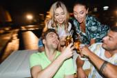 Selektivní zaměření párových přípitků s pivem během párty venku v noci