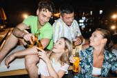 Fiatal pár pohárköszöntő sörrel közeli barátok szabadban éjszaka
