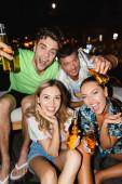 Selektivní zaměření přátel s lahvemi piva baví venku v noci
