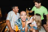 Selektivní zaměření vzrušené ženy s lahví piva při pohledu na kameru v blízkosti přátel venku v noci