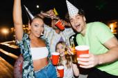 Selektivní zaměření mladých lidí ve stranických čepicích s lahvemi piva a jednorázové poháry venku v noci