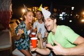 Selektivní zaměření muže v čepici strany ukazuje na jednorázové pohár vedle přátel v noci