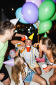 Selective focus of man holding disposable cup near friends pouring beer and balloons outdoors at night