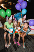 Mladí přátelé se dívají na kameru, zatímco připíjejí s pivem v blízkosti balónů a bazénu v noci
