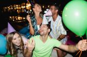Szelektív fókusz a barátok szórakozás közben party léggömbök szabadban éjszaka