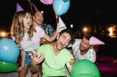 Selektivní zaměření mladých lidí držících balónky a papírové čepice v blízkosti přítele v noci