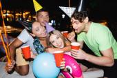 Selektivní zaměření přátel v party čepice držící jednorázové poháry v blízkosti balónky v noci