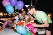 Szelektív fókusz a nők csattogó eldobható csészék közelében léggömbök party közelében uszoda éjjel