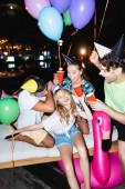 Szelektív fókusz a nő kezében eldobható csésze közelében barátok party sapkák és lufik éjszaka